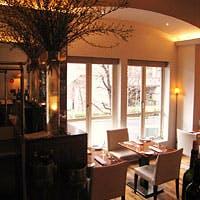 白と茶色が基調のシックな店内、遊び心ある壁一面の絵画、ガラス張りのワインセラー