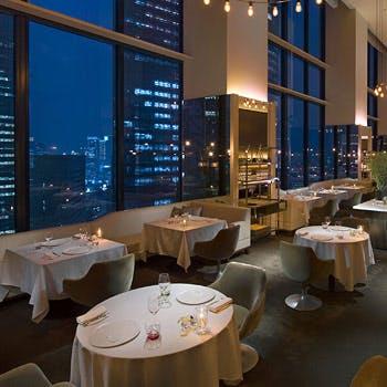 窓からのダイナミックな高層ビル群と躍動感溢れるオープンキッチンを臨む景観