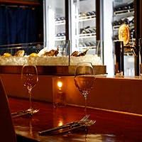 カウンター奥のシャンパンセラーに並ぶシャンパーニュを中心にワイン100種類以上