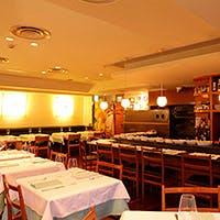 オープンキッチンの活気のある店内、温かいイタリアモダンな雰囲気