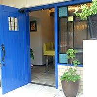真っ白な壁に真っ青な扉とキラリと輝くステンドグラス