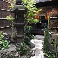 町屋造りの空間で、石灯籠がある和風庭園を眺めながら食事を楽しめる
