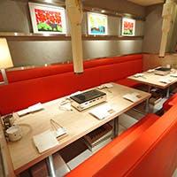 ナチュラルなインテリアに深紅のシートが映える、居心地の良いカフェのような空間